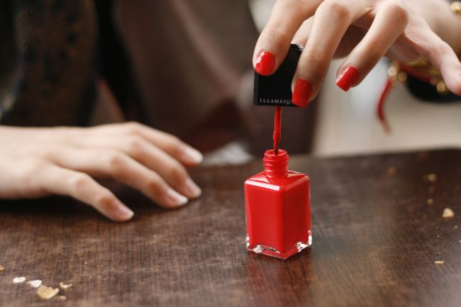 Red nail polish in application